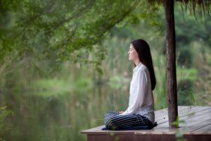 Осознанность Девушка медитирует на открытой веранде