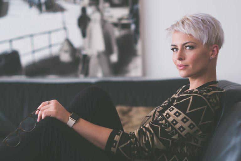 Сидящая женщина с короткой стрижкой смотрит