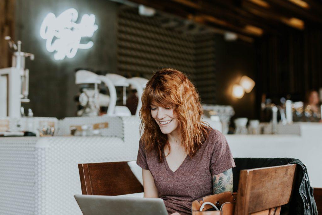 Радостная девушка записывается на курсы на ноутбуке