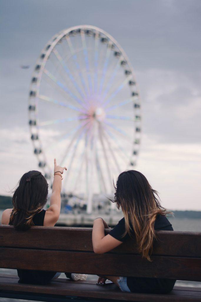 Девушки на отдыхе смотрят на колесо обозрения