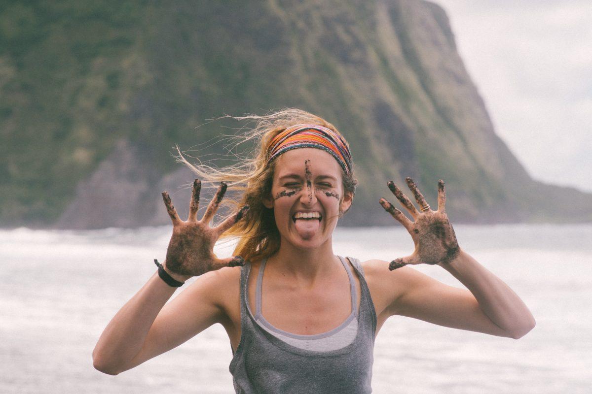 Радостная девушка показывает свои ладони в песке
