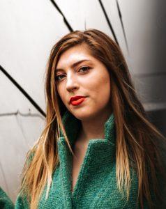 Девушка с длинными волосами и зеленом пальто