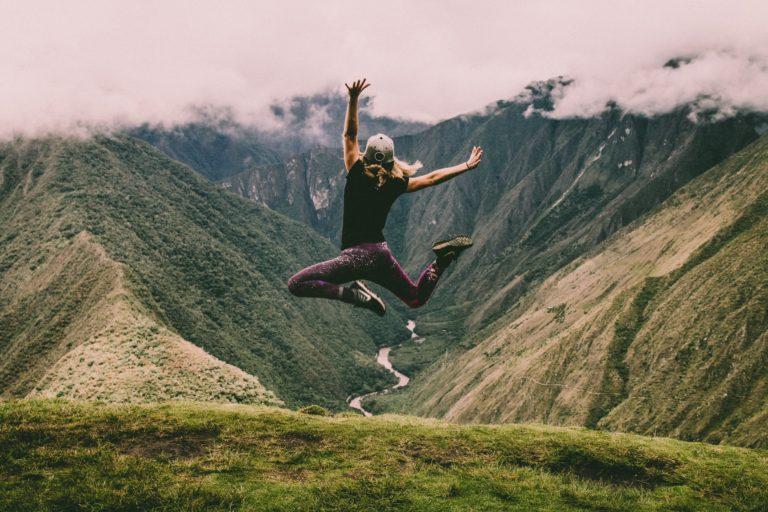 Прыжок в горах на фоне гор и горной дороги